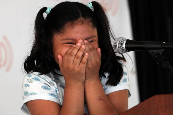 Catherine Galvan, 9, an 826Chi student writer, is all giggles as she tries to read her story at the Printers Row Lit Fest in Chicago in 2011.