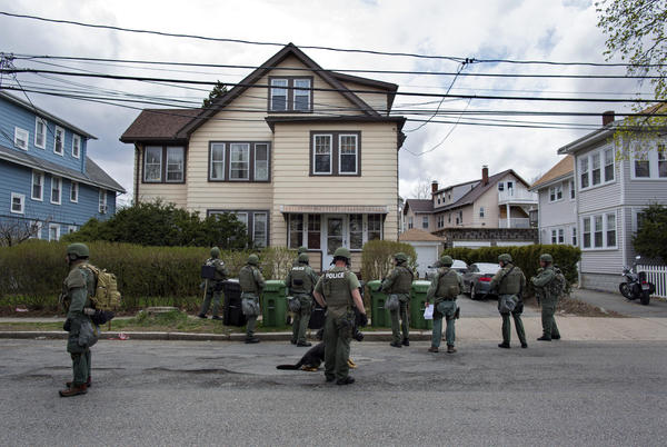 Heavily armed police officers perform house-to-house searches in Watertown, Mass., as they look for one of two suspects in the Boston Marathon bombings.