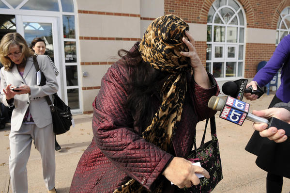 Candace Bednarz covers her face with a scarf as she leave Manchester Superior Court after the arraignment of her brother, Brett Bednarz for the 2010 murder of their mother, Beverly Therrien, and two tenants at their home in East Hartford.