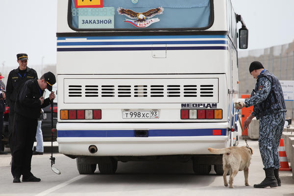 A police officer with a dog and security guards check a bus on April 16 entering the Olympic Park that is under construction for the 2014 Winter Games in the Black Sea resort of Sochi, Russia.