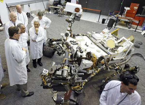 Scientist and engineers stand next to a duplicate of the Mars Rover Curiosity at JPL.
