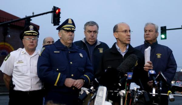 Officials address the media during a news conference in Watertown, Mass., on Friday. CNN has seen huge ratings gains this week.