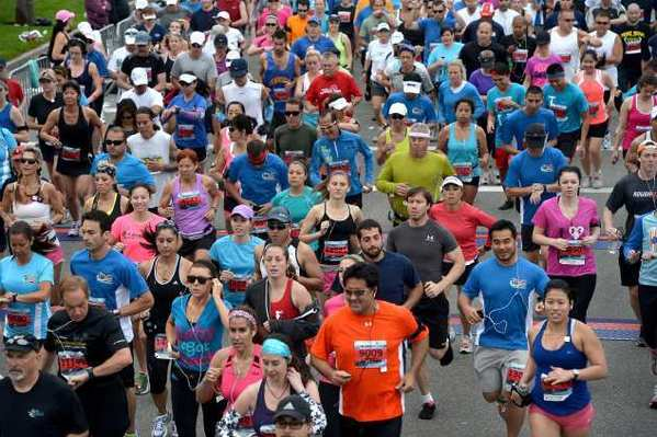 Runners take off from the starting line of the OC Half Marathon at Fashion Island last year.