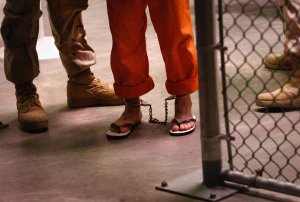 "A ""non-compliant"" detainee is escorted by guards after showering inside the U.S. military prison for ""enemy combatants"" on October 27, 2009 in Guantanamo Bay, Cuba. Although U.S. President Barack Obama pledged in his first executive order last January to close the infamous prison within a year's time, the government has been struggling to try the accused terrorists and to transfer them out ahead of the deadline. Military officials at the prison point to improved living standards and state of the art medical treatment available to detainees, but the facility's international reputation remains tied to ""enhanced interrogation techniques"" such as waterboarding employed under the Bush administration."