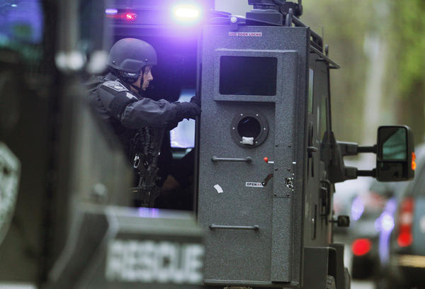 A police SWAT team member prepares to deploy from an armored personnel carrier as multiple armored police vehicles rush down the street during a police assault on a house on Franklin Street during the search for Dzhokhar Tsarnaev, the surviving suspect in the Boston Marathon bombings, in Watertown, Mass.