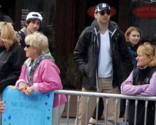 Suspects Tamerlan Tsarnaev, wearing a dark baseball cap, and Dzhokhar A. Tsarnaev, behind him wearing a white baseball hat, walk among those watching the Boston Marathon.