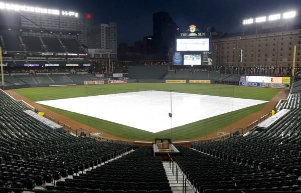 The infield at Camden Yards is covered by a tarp as rain falls Friday evening.