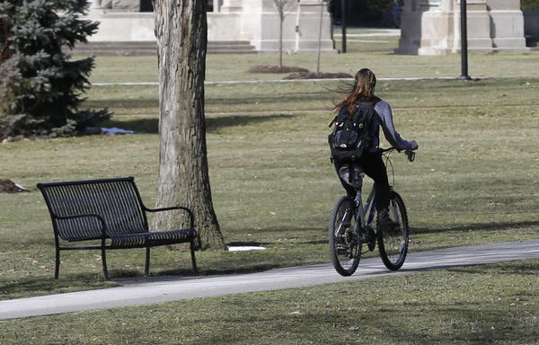 A student rides a bicycle on the campus of Oberlin College.