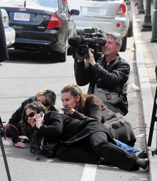 Journalists take cover during the manhunt for the second suspect of the Boston Marathon bombing in Watertown, Mass. Some traditional media got caught up in the frenzy of online speculation used incorrect information from anonymous posters.
