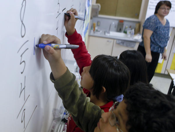 Teacher Maria Duarte watches from a distance while her students solve fraction problems on the board in her math class at Los Angeles Elementary School.
