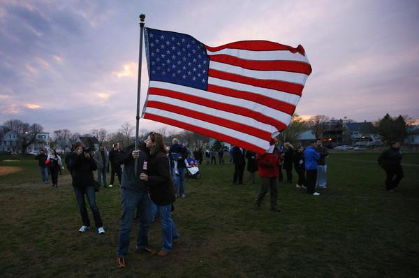 "Neighbors hug under a U.S. flag as they arrive for a candlelight vigil in the Dorchester neighborhood of Boston, Massachusetts April 16, 2013 where eight-year-old Boston Marathon bombing victim Martin Richard lived. A Little League baseball player, Martin lived in the blue Victorian house in working-class Dorchester - a Boston neighborhood dotted with ""Kids at Play"" traffic signs and budding trees - with his parents Bill and Denise, sister Jane, 7, and brother Henry, 10. Bill Richard told the world in an email on Tuesday that his son had been killed when bombs exploded at the marathon finish line. Martin's mother and sister were seriously injured."