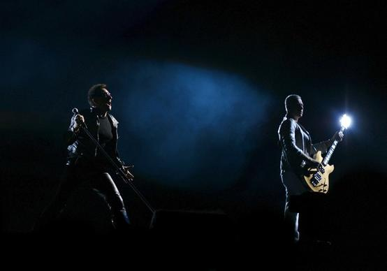 Lead singer Bono of U2 performs alongside bass guitarist Adam Clayton during the 360-Degrees Tour concert at the Estadio Anoeta on September 26, 2010 in San Sebastian