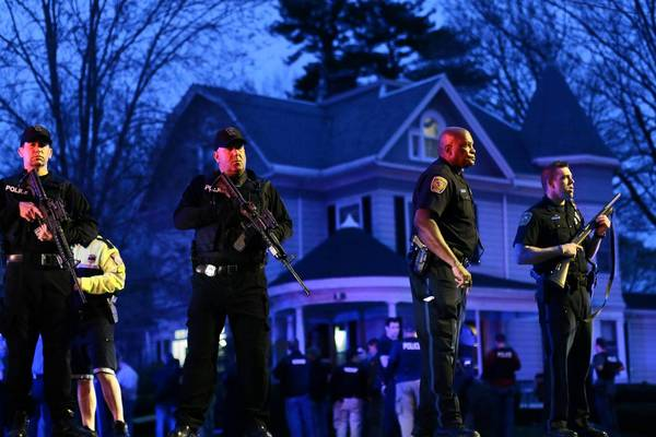 Police officers guard a Watertown, Mass., neighborhood as a daylong manhunt closes in around the second Boston Marathon bombing suspect. He was found hiding in a boat in a resident's backyard.