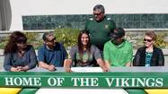 Joanna Larios (center) smiles as Athletic Director Steve Cato (standing) and family members look on during her signing.