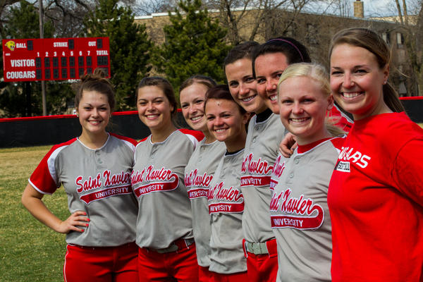 Sarah Saunders (from left) with twin sister Samantha Saunders, Erin Houlihan, Katie Houlihan, Nicole Nonnemacher, Megan Nonnemacher, Kate Mollohan and her sister, assistant coach Erin Mollohan at practice for the Saint Xavier women's softball team.
