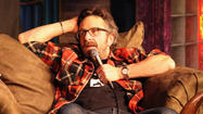 Marc Maron slips into a chair and plunks a tattered, spiral-bound notebook onto the table. The cover, folded back, reveals dense, tight scribbling on ruled paper. Pen in hand, Maron hunches over the notes, looks up for a second to lock eyes by way of greeting, then drops his head back down.