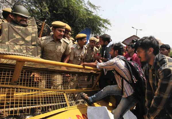 Protesters attempt to pull down a barricade outside police headquarters in New Delhi, where hundreds staged an angry demonstration after the kidnapping and rape of a 5-year-old girl.