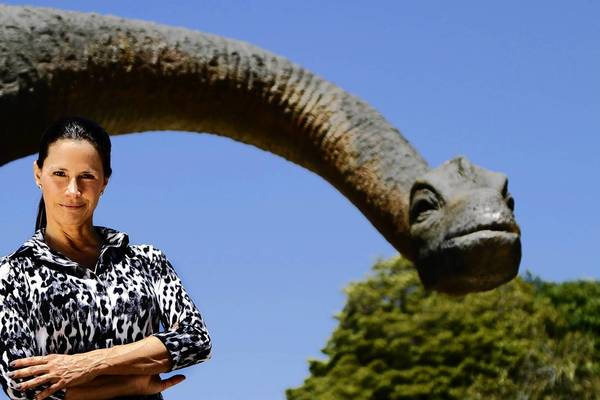 Carolyn Franks, owner of the Zoomars petting zoo on historic Los Rios Street in San Juan Capistrano, stands in front of Juan the Capistrano Dinosaur. Detractors say the 40-foot apatosaurus statue is an eyesore that has no place in the city, and Juan is scheduled to be shipped to a tourist attraction in Arizona.