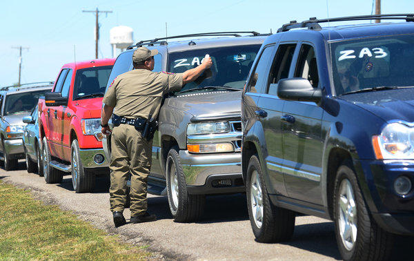 A Texas highway patrol officer marks a vehicle Saturday as residents are allowed to return temporarily to their destroyed homes near the site of the fertilizer plant blast in West, Texas.