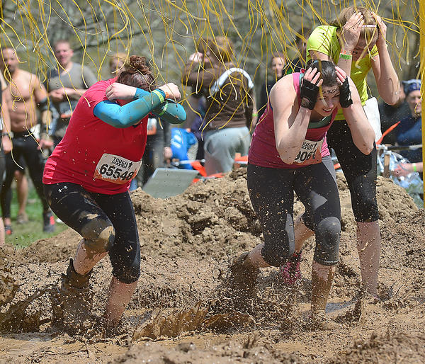 "Runners take on the last obstacle called ""Electroshock Therapy"" in the Mid-Atlantic spring 2013 Tough Mudder course at Peacemaker National Training Center in Gerrardstown, W.Va., Saturday."