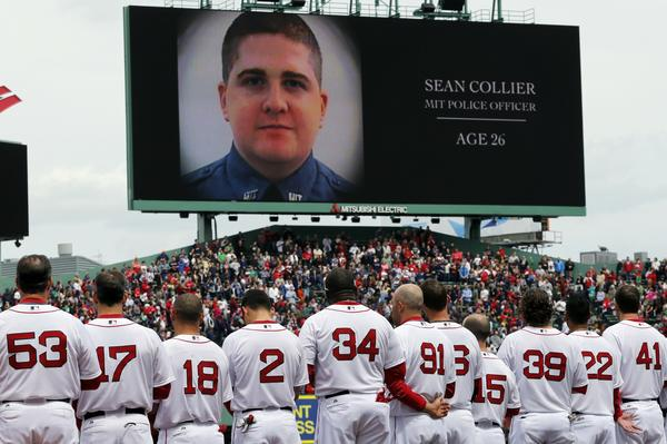 As members of the Boston Red Sox pay tribute to victims of the Boston Marathon attack and its aftermath, an image of slain MIT police officer Sean Collier is displayed on the scoreboard before Saturday's game at Fenway Park.