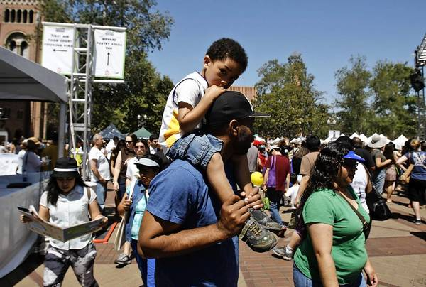 Collin Hinds carries his son Preston, 4, during the Los Angeles Times Festival of Books at USC.