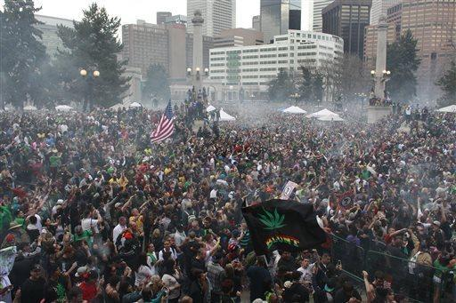 Members of a crowd numbering tens of thousands smoke marijuana simultaneously at 4:20 p.m. at the Denver 4/20 pro-marijuana rally. But gunfire erupted, injuring three and spoiling the mood.