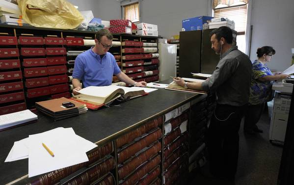 Men who declined to give their names and the name of their employer look at mineral rights records at the Wayne County clerk's office in Fairfield, Ill.