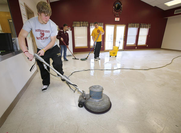 Northern State University football players Tyson Zemlicka, left, along with Gavin Larsen, back center, and Chad Stoterau work to put a new coat of wax on a floor at the New Beginnings Center during Saturday's Day of Champions event.
