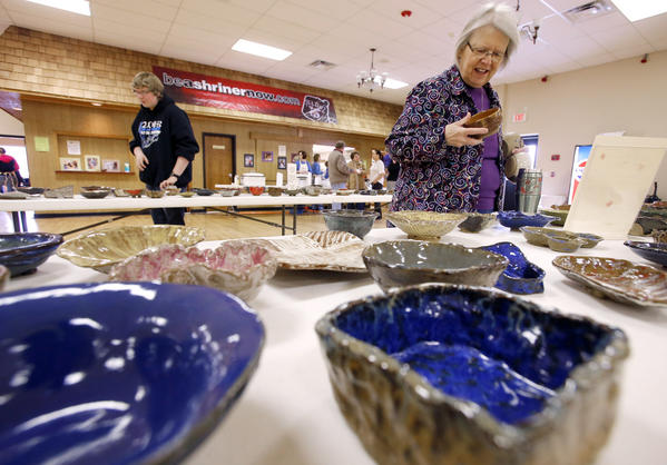 Muriel Mattson of Aberdeen looks over one of the many bowls to choose from at the Empty Bowls event Saturday at the Yelduz Shrine Center. At the table in the background at left is Lucas Miller. Guests attending the soup lunch made a donation and chose a bowl made by area residents to take home as a reminder that hunger exists.