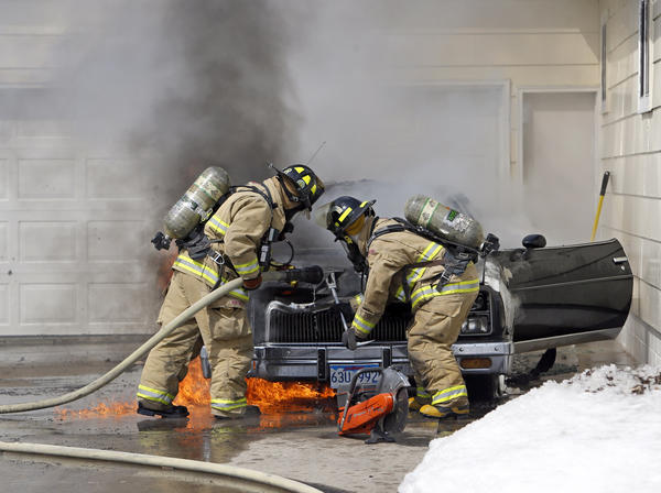 Firefighters Lance Hammrich, left, and Ryan Webb -- both with Aberdeen Fire and Rescue -- work to open the hood of a car that burned Saturday in the 1000 block of South Lawson Street.