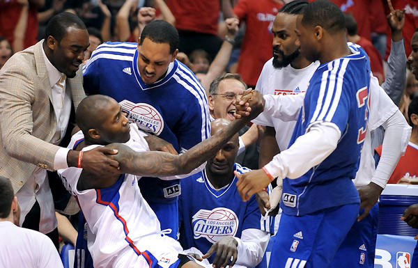 Clippers guard Jamal Crawford is helped by teammate after getting fouled while making a three-point shot in the first half Saturday night.