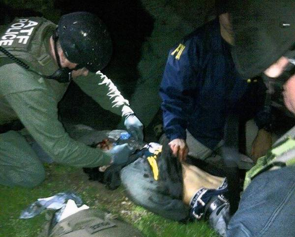 Federal agents check Dzhokhar Tsarnaev for explosives while giving him medical attention after a daylong manhunt in Watertown, Mass.