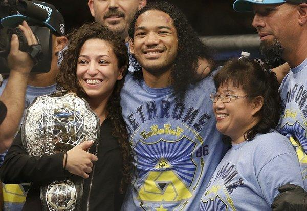 "Benson Henderson celebrates with his fiancee, Maria Magana, and mother, Song Henderson, after a split-decision victory over Gilbert Melendez in a lightweight championship bout at ""UFC on Fox 7"" in San Jose."