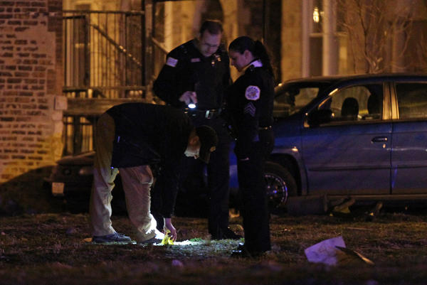 An evidence marker is placed on a lawn at the corner of Fifth and Francisco Avenues after a man was shot in the area Sunday morning, April 21, 2013, in Chicago. He was transported to Mount Sinai Hospital.