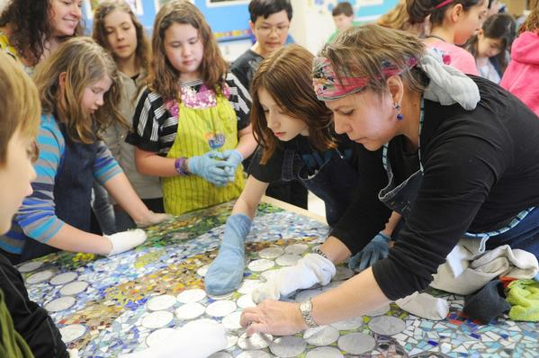 In a photo from February, visiting artist Carien Quiroga, right, works with students on a mosaic mural to commemorate the school's tenth anniversary. On Monday, Folly Quarter will be formally recognized as a Maryland Blue Ribbon School.