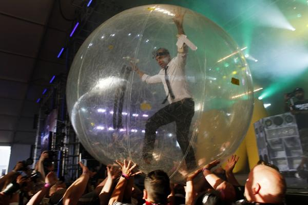 Walshy Fire, of the musical project Major Lazer, runs across the crowd in a plastic ball during Lazer's show in the Mojave Tent at Coachella.