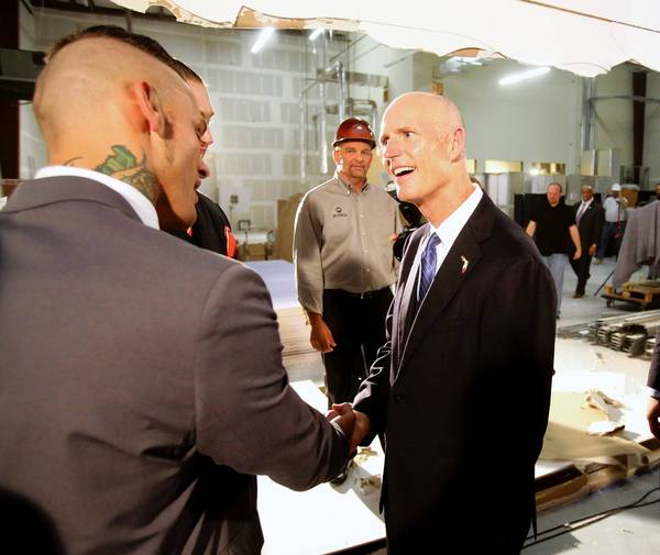 Gov. Rick Scott shakes hands with World Wrestling Entertainment wrestler Corey Graves at the announcement of a new WWE performance center coming to Orlando, Thursday, April 18, 2013. (Joe Burbank/Orlando Sentinel)