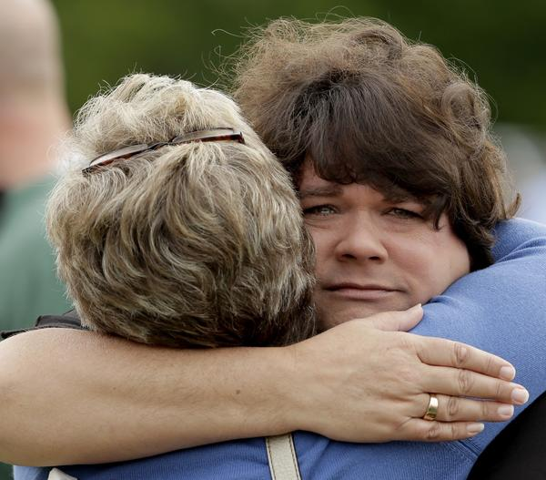Lisa Crowder, facing camera, is hugged by a friend before a First Baptist Church service held in a field four days after an explosion at a fertilizer plant in West, Texas. Crowder's home was destroyed in the massive explosion.
