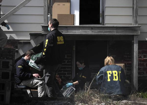 FBI agents label and remove boxes of documents from a storage house behind the scandal-stricken Sacred Heart Hospital on Chicago's West Side on Tuesday.
