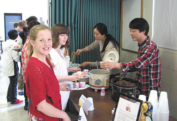 From left, are sixth-graders Savannah Placie and Alexis Kirk who were served South Korean food by Mr. and Mrs. Daniel Kim.