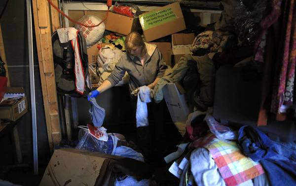 Lori Scott helps sort water-soaked belongings in the basement of her family's home on Oakwood Avenue near White Street in Des Plaines.