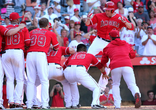 Angels designated hitter Mark Trumbo arrives at home plate with a leap into awaiting teammates after hitting the game-winning home run against the Tigers in the 13th inning Sunday afternoon in Anaheim.