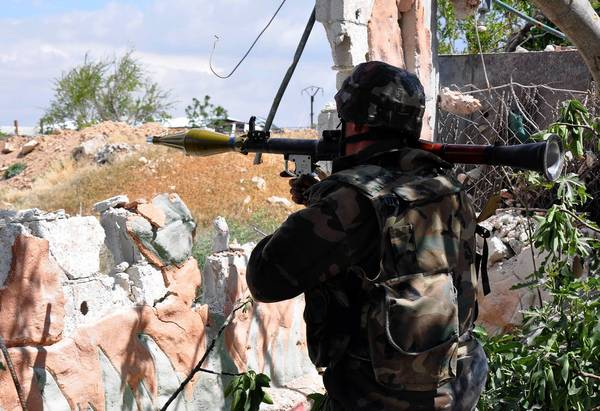 A Syrian soldier takes position during a patrol in a rural area of Damascus in an undated photo.