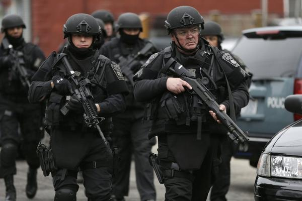 In Watertown, Mass., police in tactical gear search for a suspect in the Boston Marathon bombings.