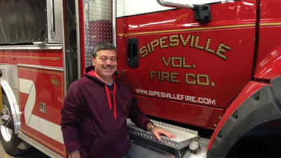 Jim Shroyer poses with the Sipesville fire truck where he has served for 35 years.