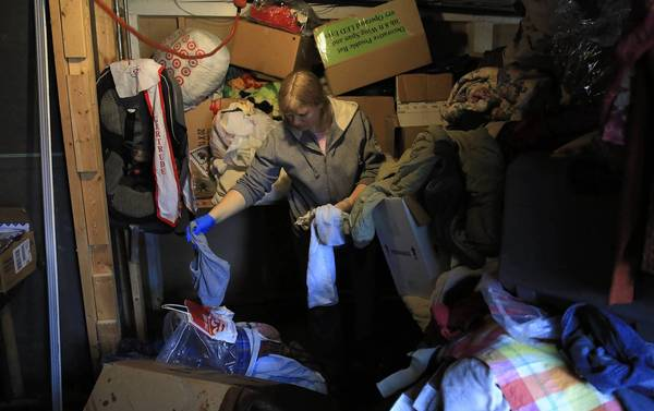 Lori Scott helps sort soaked belongings in the basement of her family's home Sunday in Des Plaines after last week's flooding.