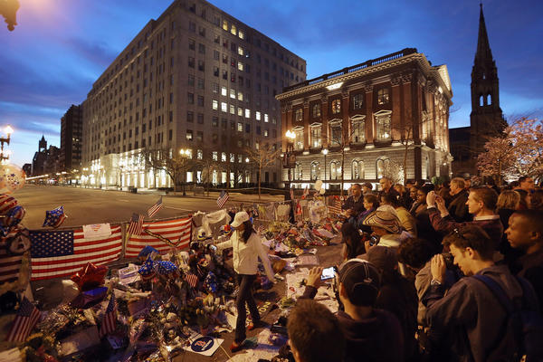 People gather at a makeshift memorial for victims near the site of the Boston Marathon bombings at the edge of the still-closed section of Boylston Street a day after the second suspect was captured on April 20, 2013 in Boston, Massachusetts. A manhunt for Dzhokhar A. Tsarnaev, 19, a suspect in the Boston Marathon bombing ended after he was apprehended on a boat parked on a residential property in Watertown, Massachusetts. His brother Tamerlan Tsarnaev, 26, the other suspect, was shot and killed after a car chase and shootout with police. The bombing, on April 15 at the finish line of the marathon, killed three people and wounded at least 170.