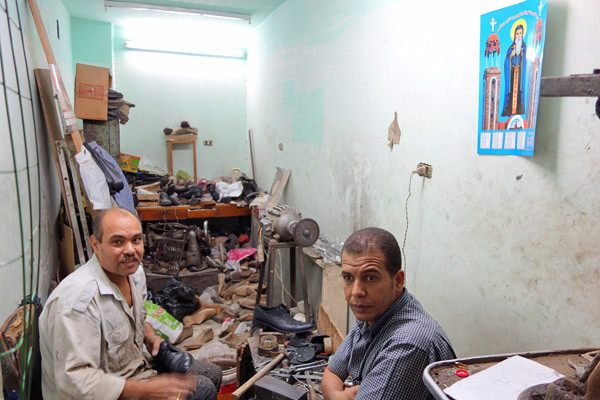 Photos: Denial in Egypt? - This Christian cobbler fixes Muslim shoes under Christian posters.