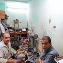 This Christian cobbler fixes Muslim shoes under Christian posters.